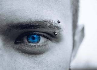 selective photo of man's blue eye