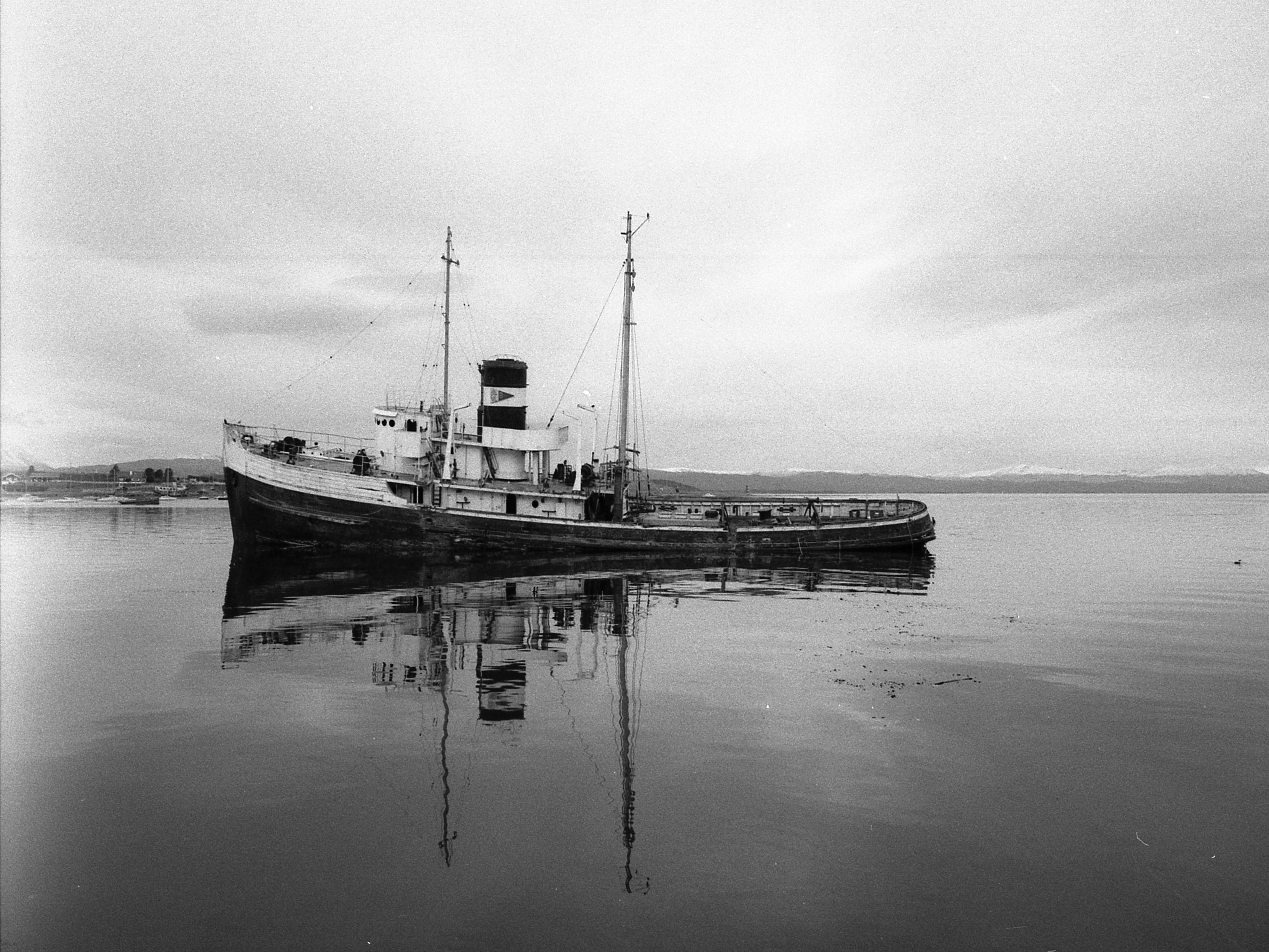 grayscale photo of fishing vessel on body of water
