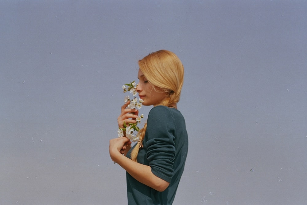 woman smelling white petaled flowers