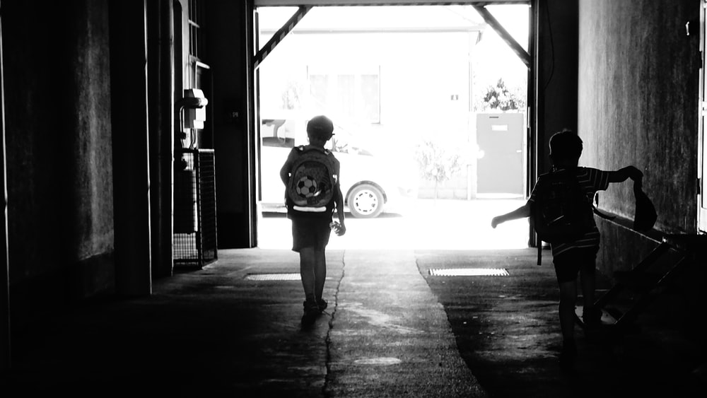 two boys walking in corridor of a building grayscale photo