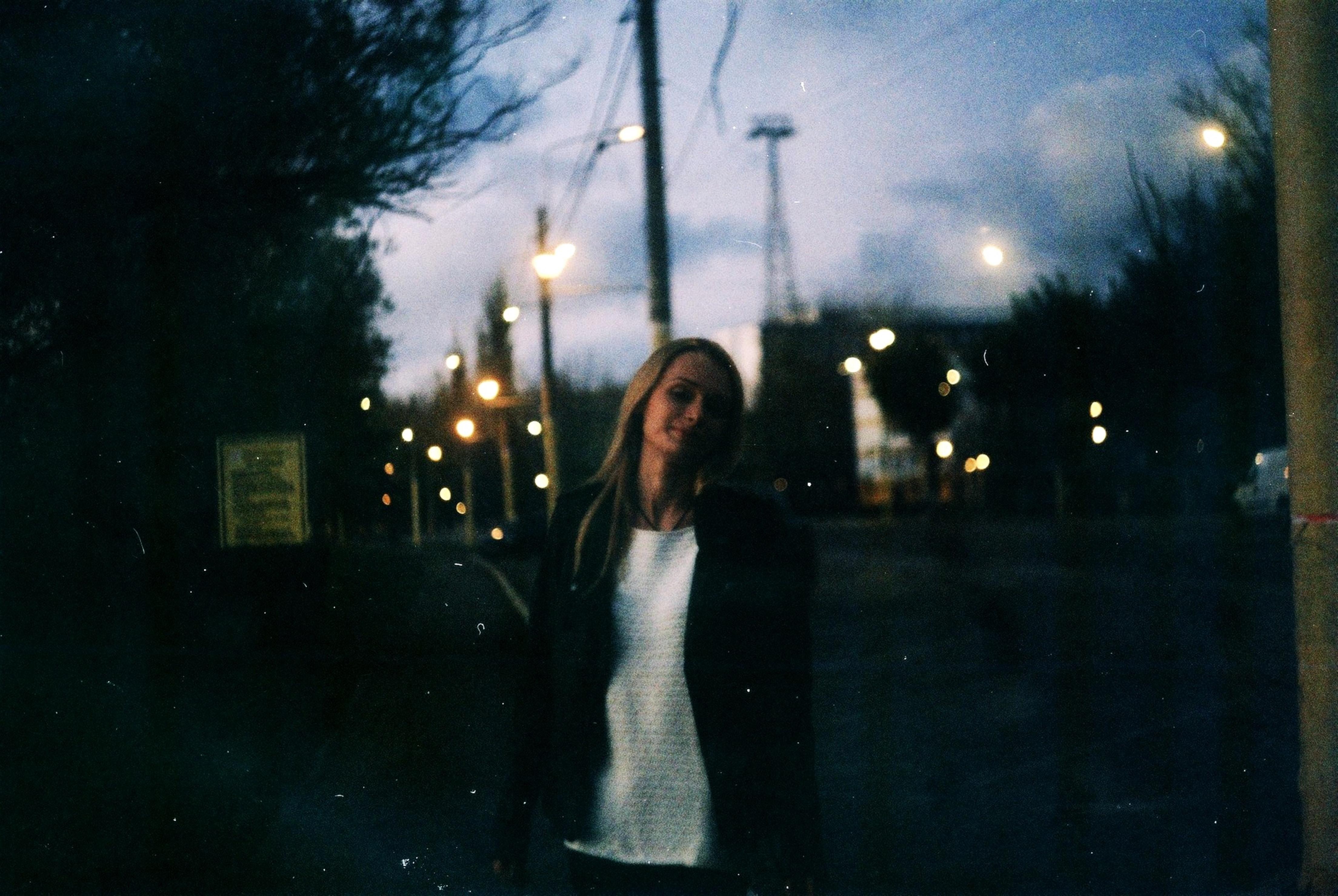 woman wearing black jacket near street lights