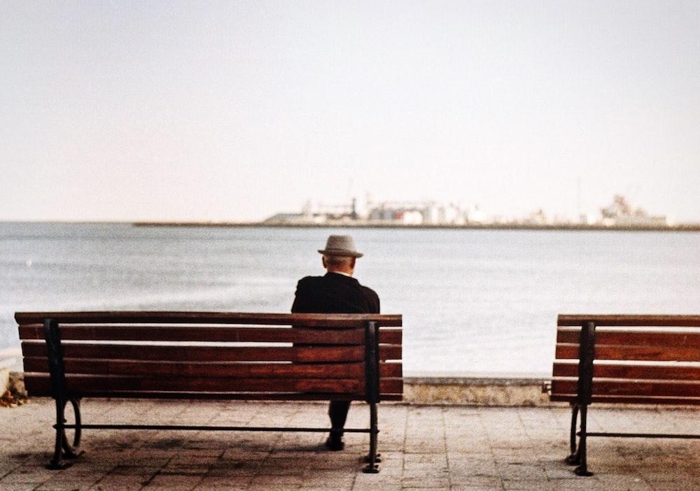 man sitting in brown wooden bench