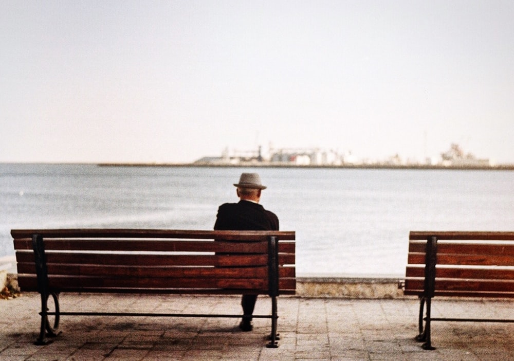 man sitting in brown wooden bench