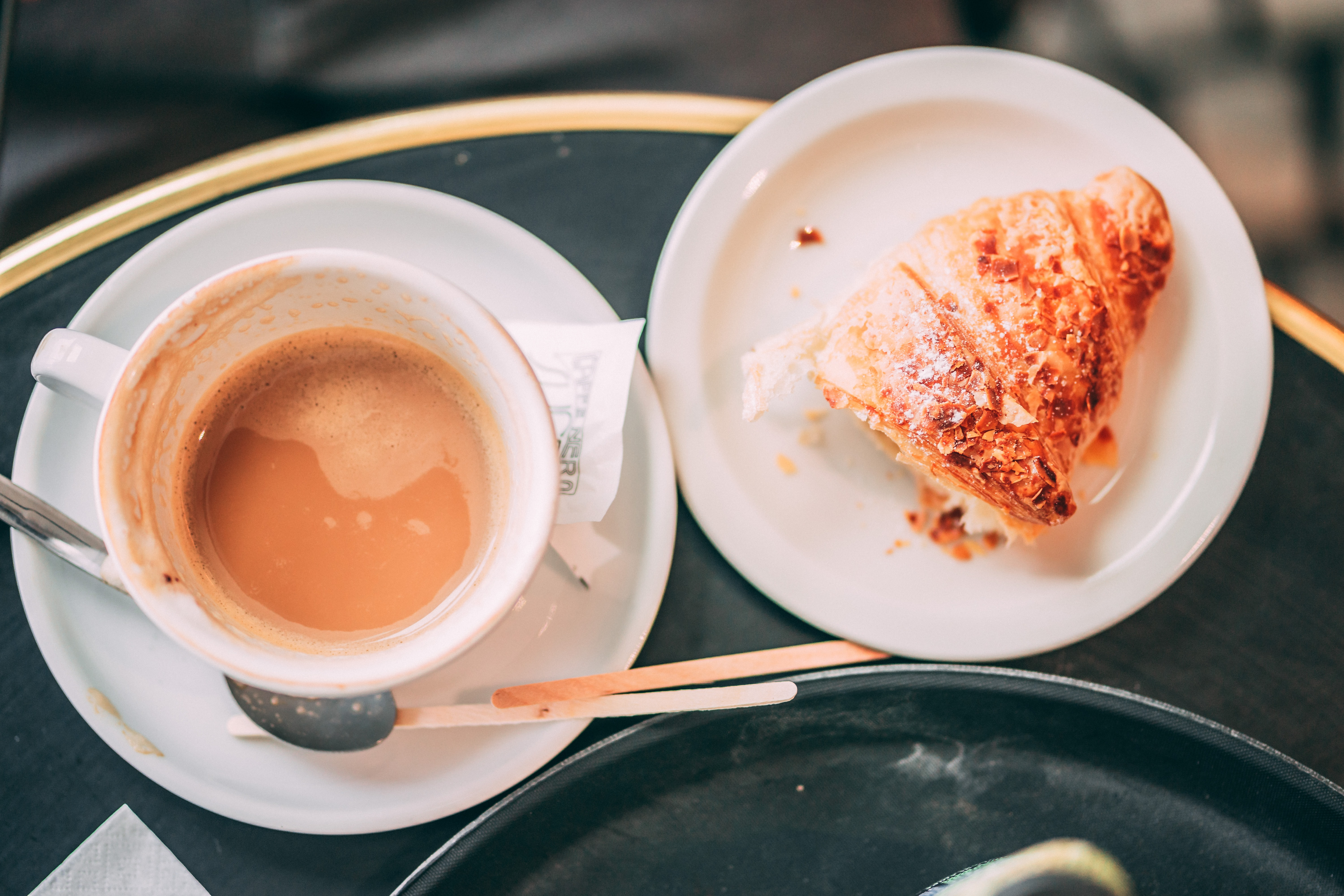 cup of coffee on table and baked bread on plate