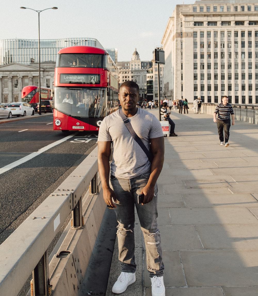 man standing beside railings and asphalt road
