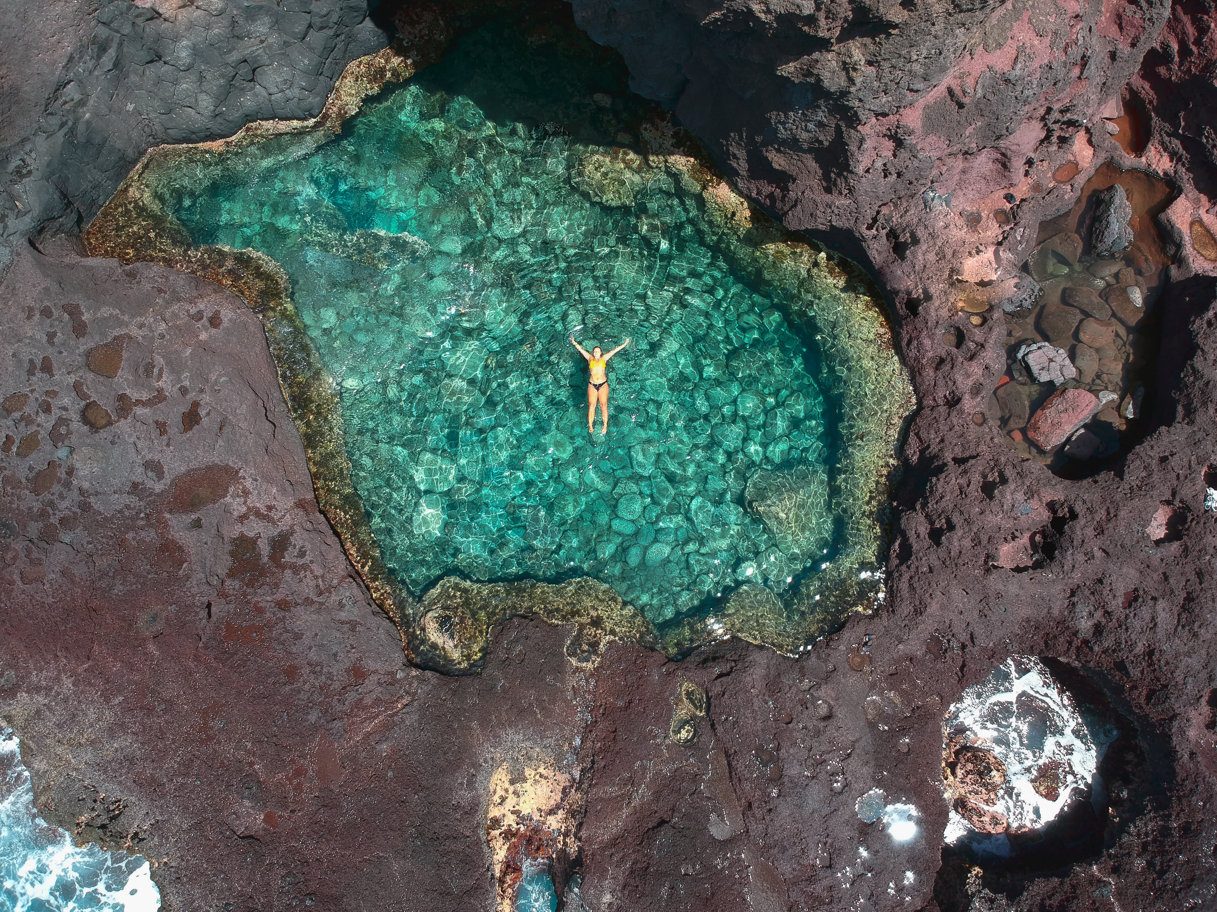 aerial photography of person floating on calm body of lake surrounded by rock during daytime