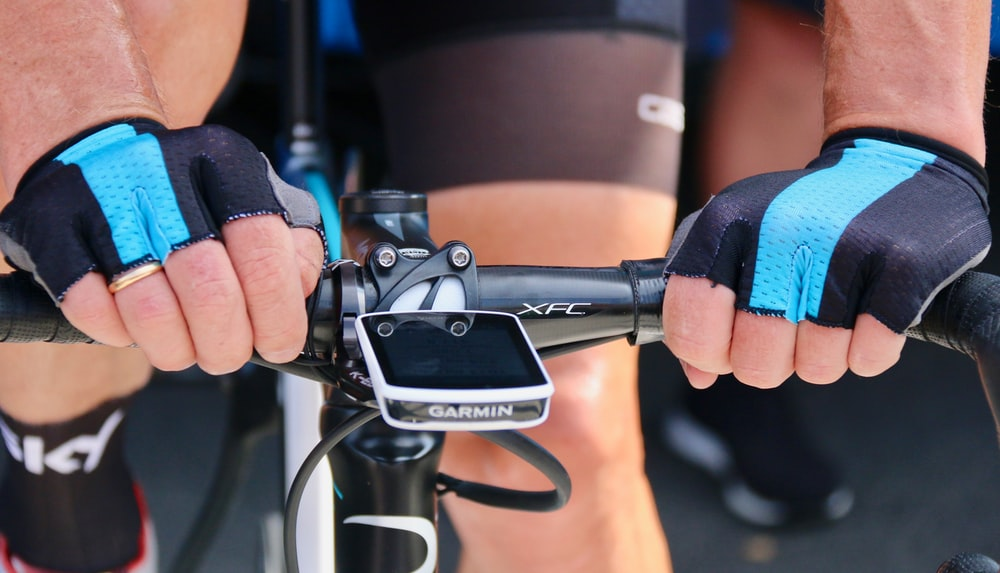 close-up photo of cyclist's hands on road bike handle bar
