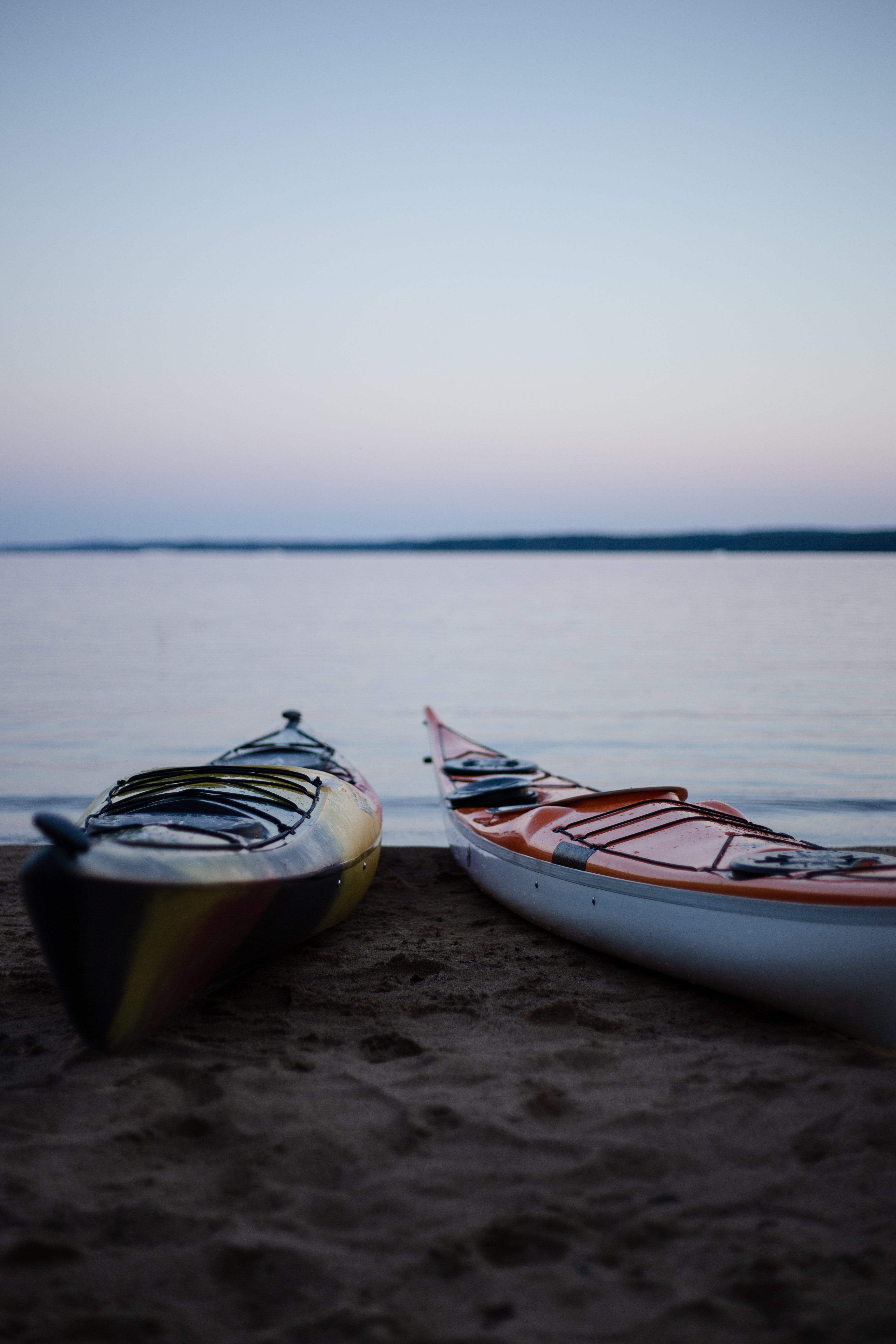 two yellow and orange canoes on beach