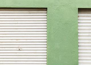 grey steel roller-shutter near green wall