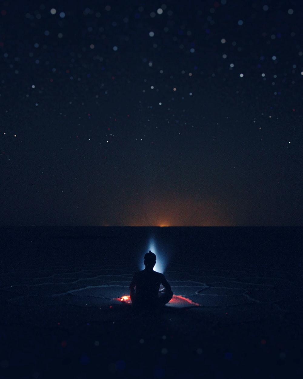 silhouette of person sitting on shore beside bonfire digital painting