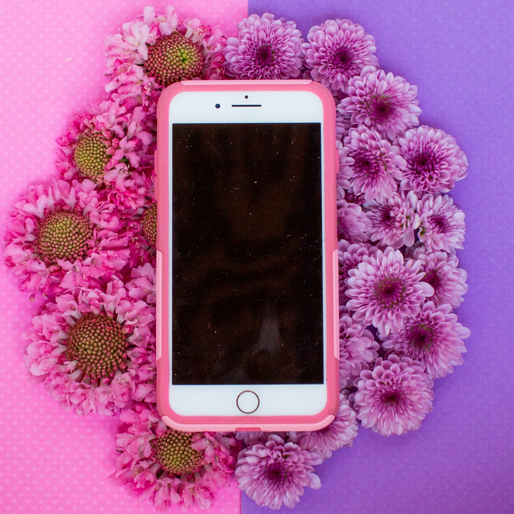 gold iPhone 6 with pink case on white flower background