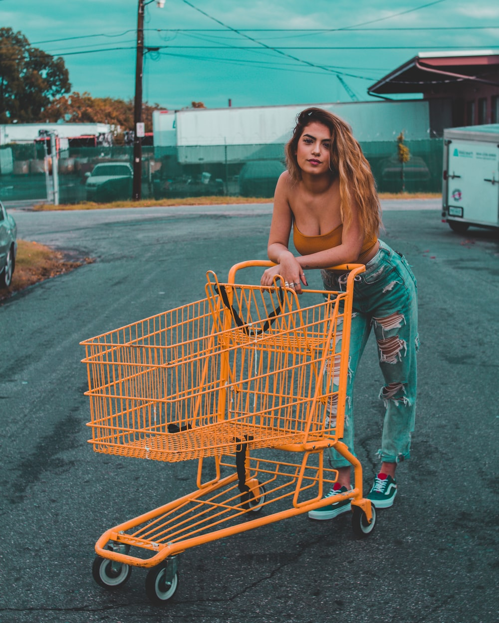 woman leaning on yellow shopping cart standing on concrete pavement during day