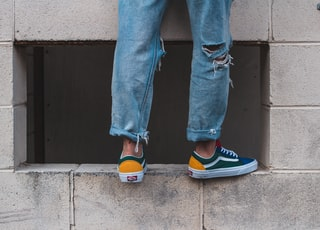 man in pair of green-and-white low-top vans