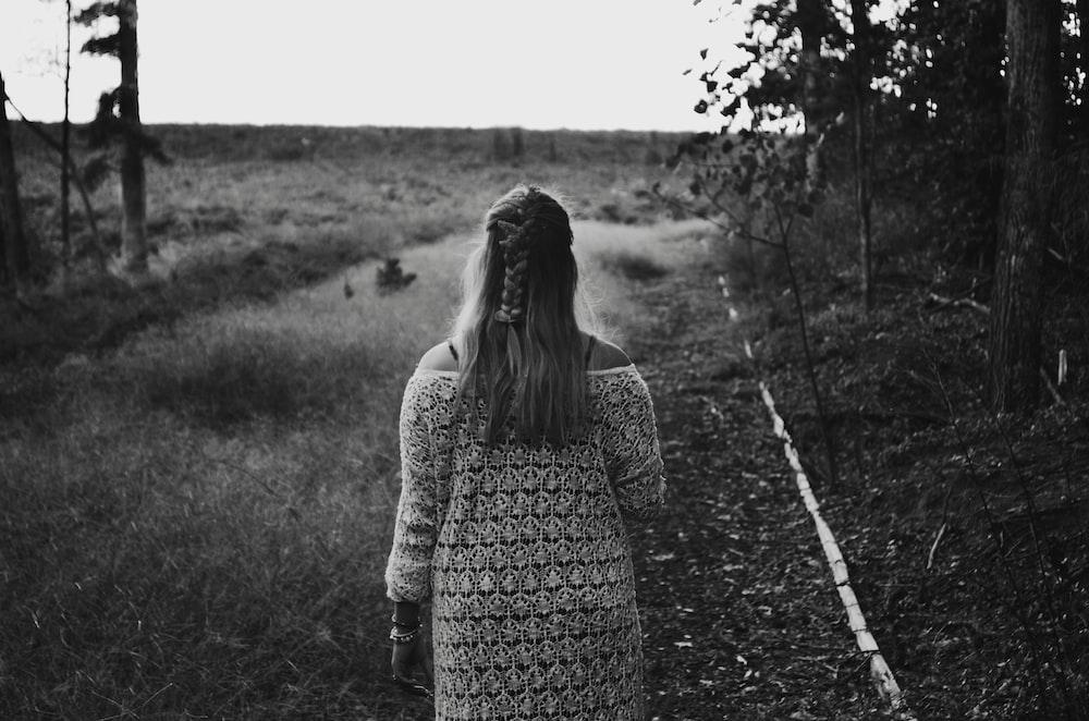 grayscale photo of woman wearing dress walking across grass field between trees