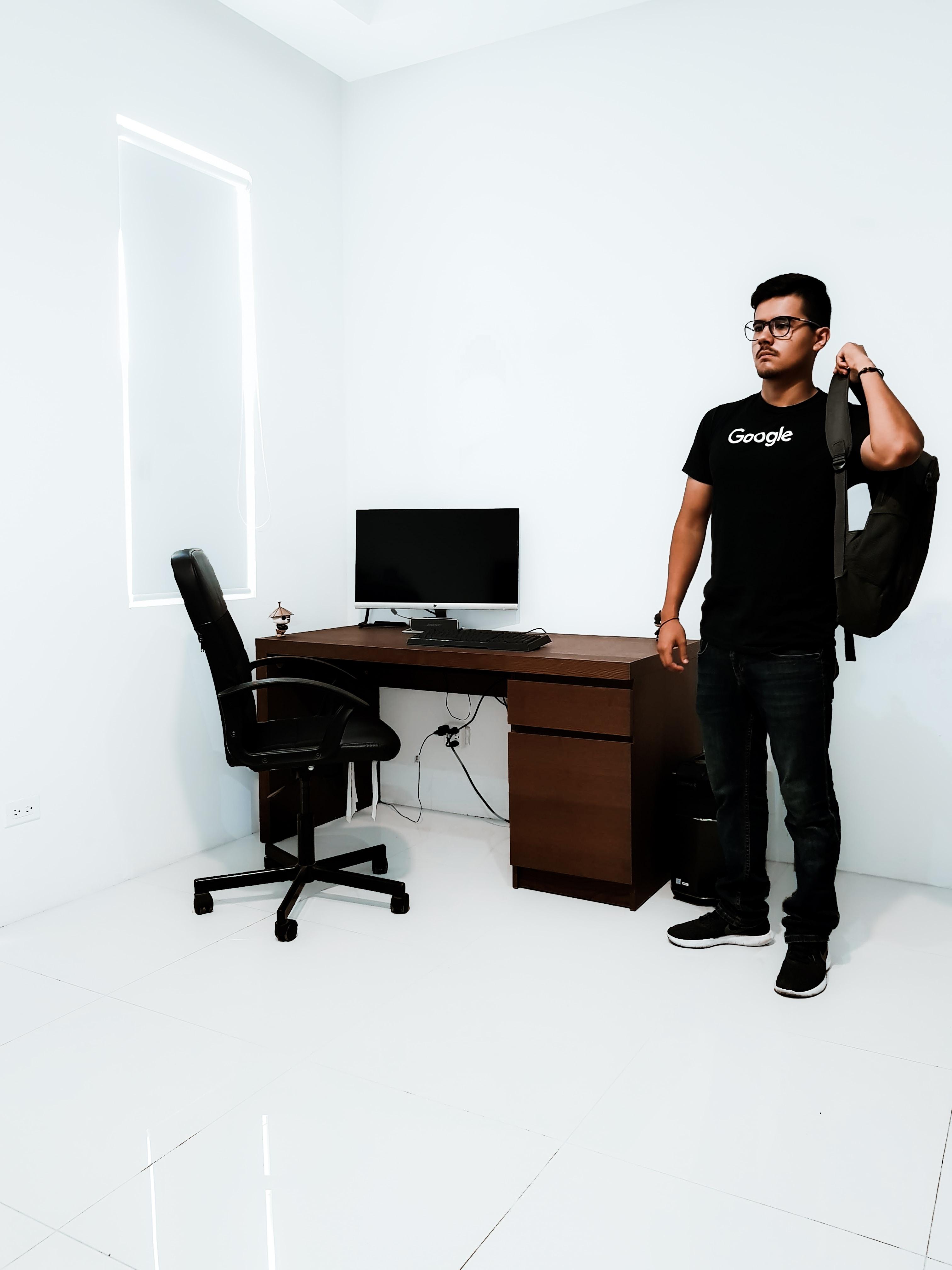 man standing near brown desk beside white wall