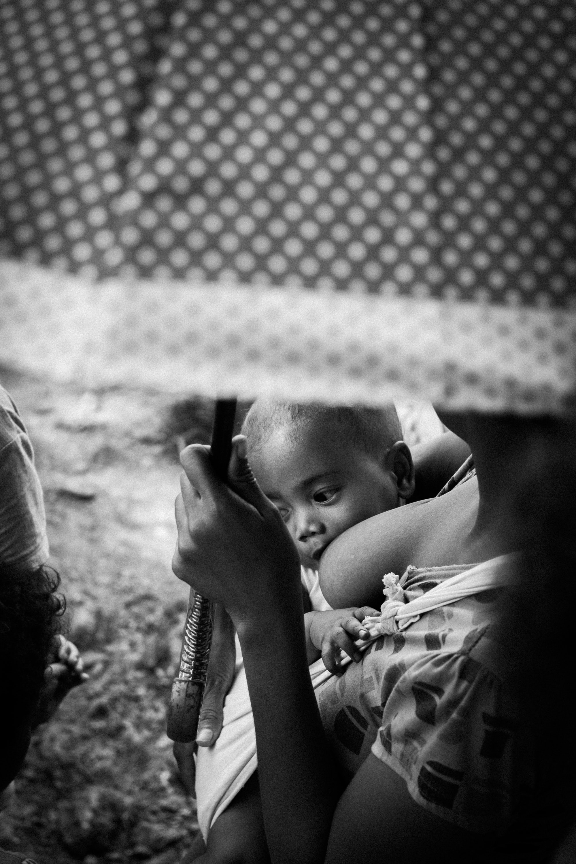 grayscale photo of breastfeeding mother with umbrella