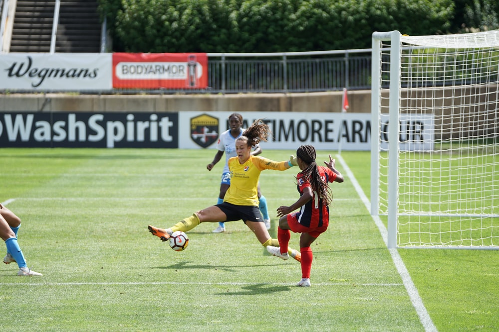 soccer player kicking ball near goal