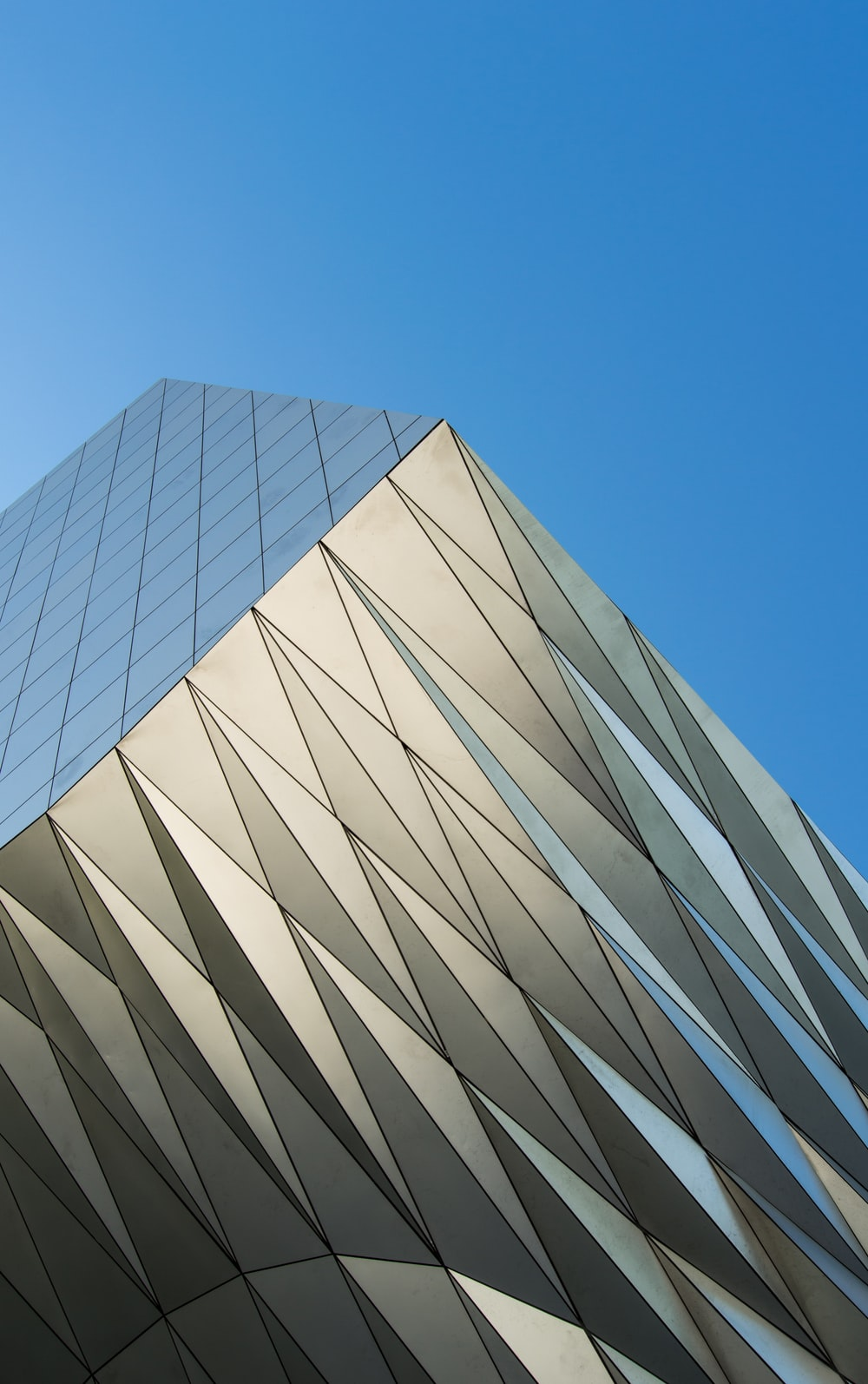 low angle photo of gray building under blue sky