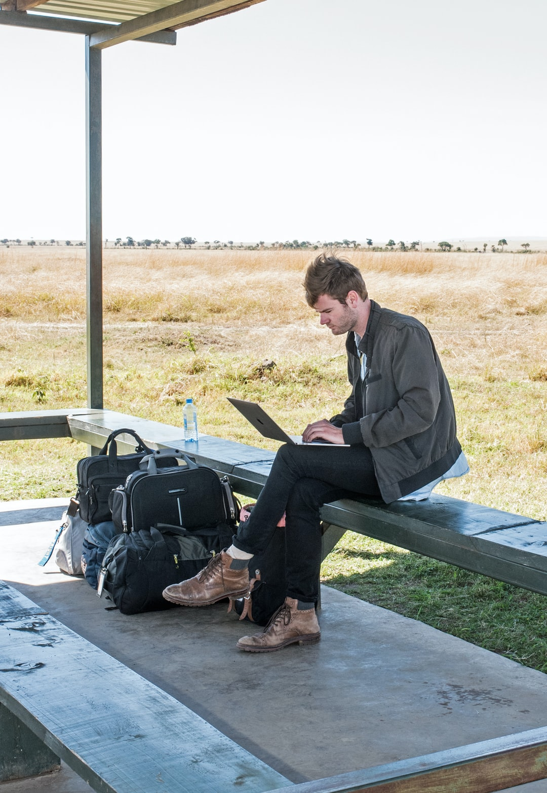 Digital addiction. A problem for many of us. While waiting for a light plane in the Masai Mara in Kenya, a man is totally engrossed in his laptop, while in real life, a lioness has made a kill a mere 100 metres from this spot.