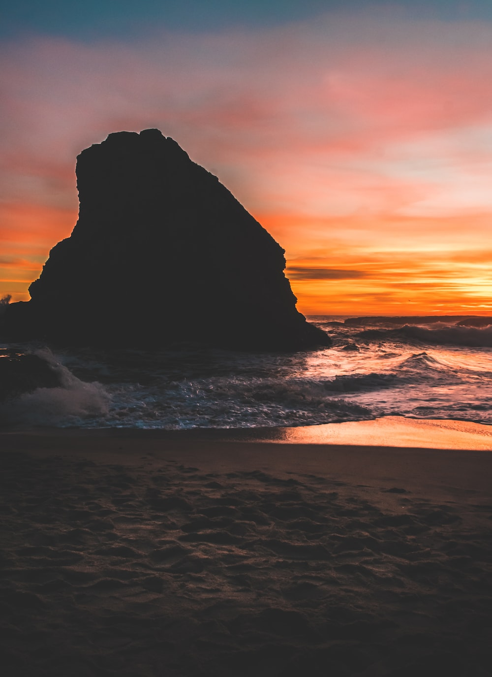 rock in body of water during sunset