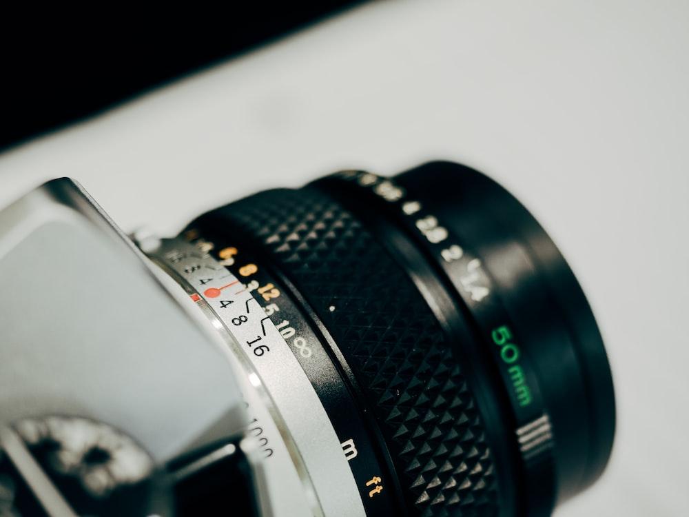 white and black DSLR camera on white surface