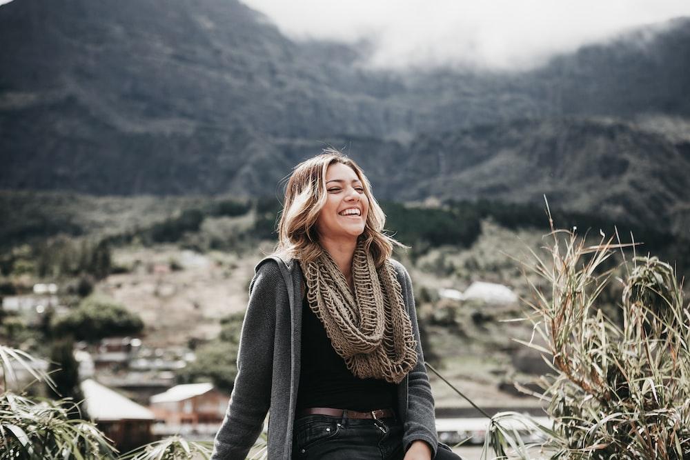 woman sitting beside grass near mountain range