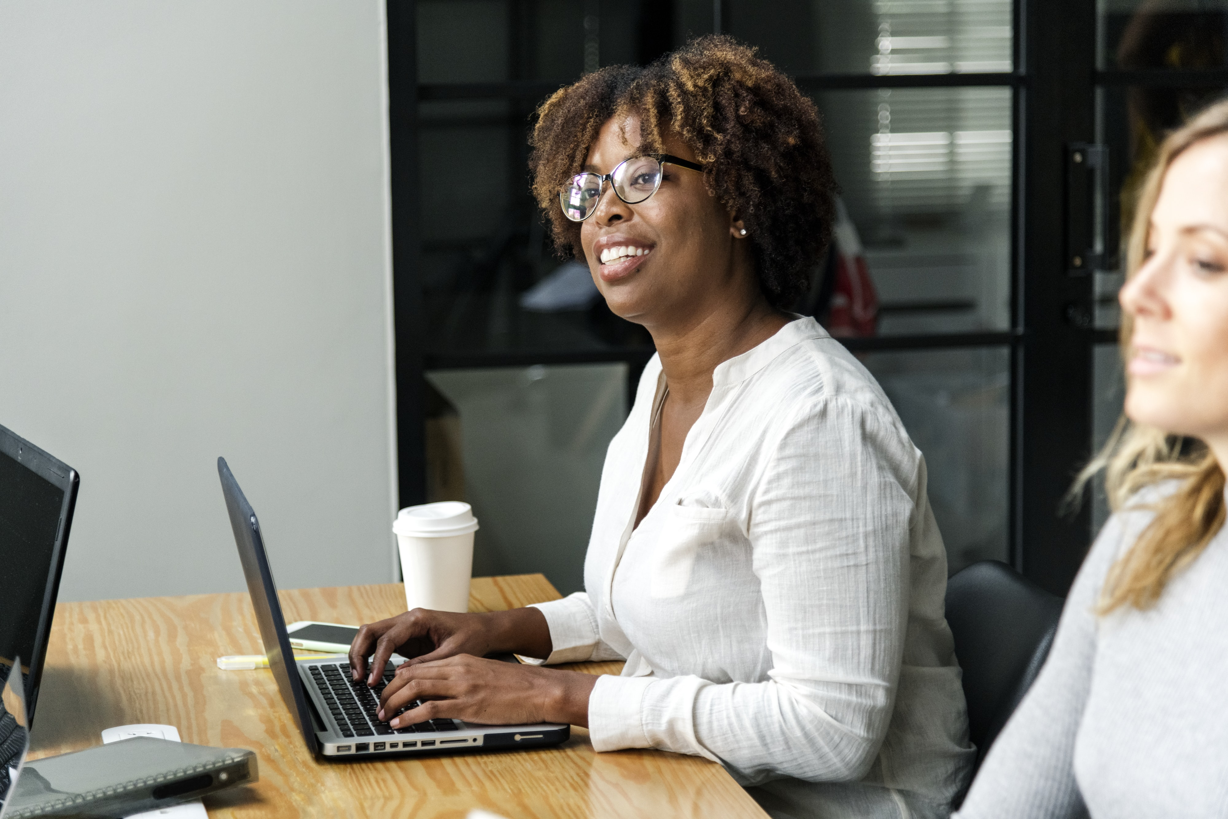 woman sitting on chair leaning on laptop computer