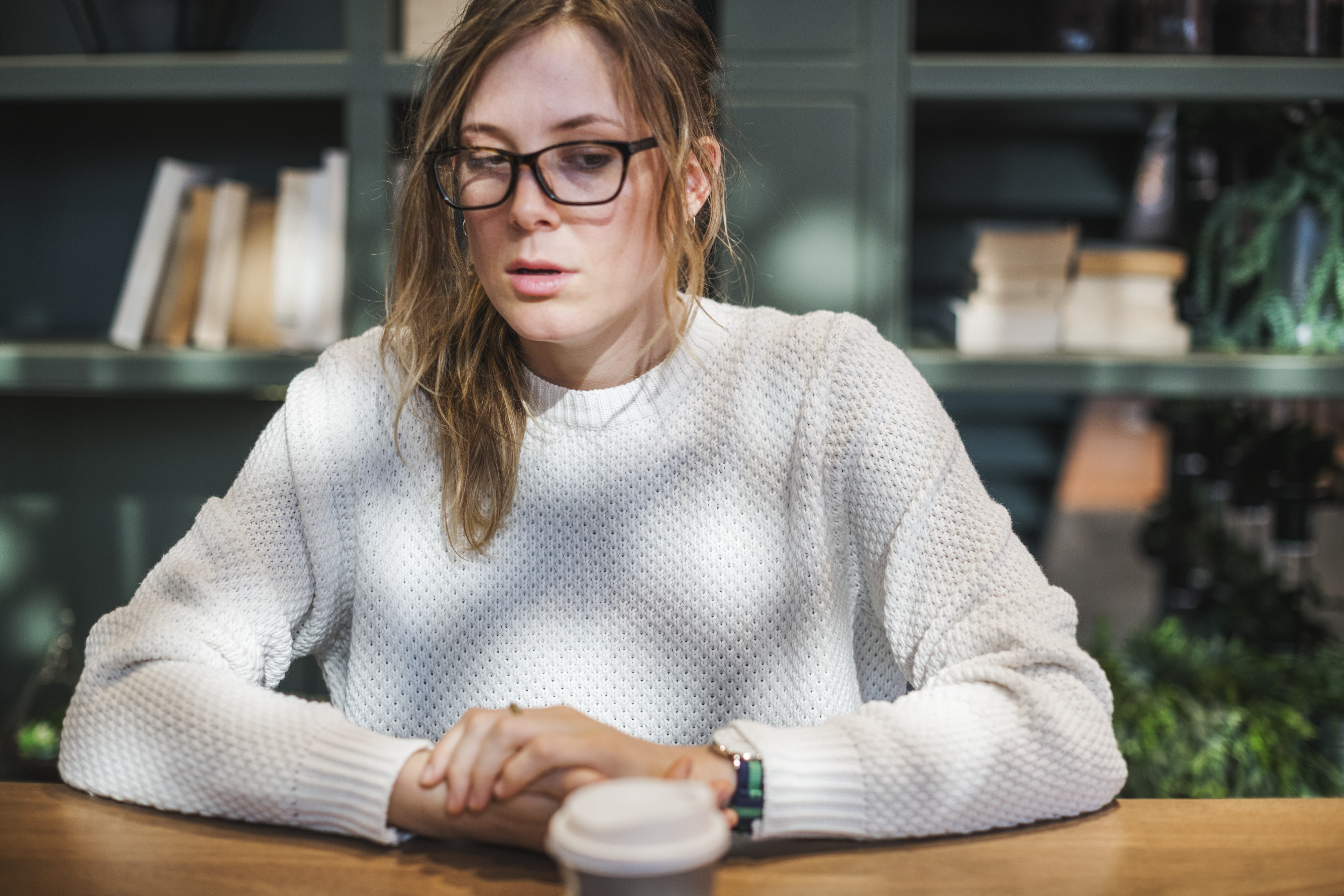 woman wearing white knit sweater sitting at table