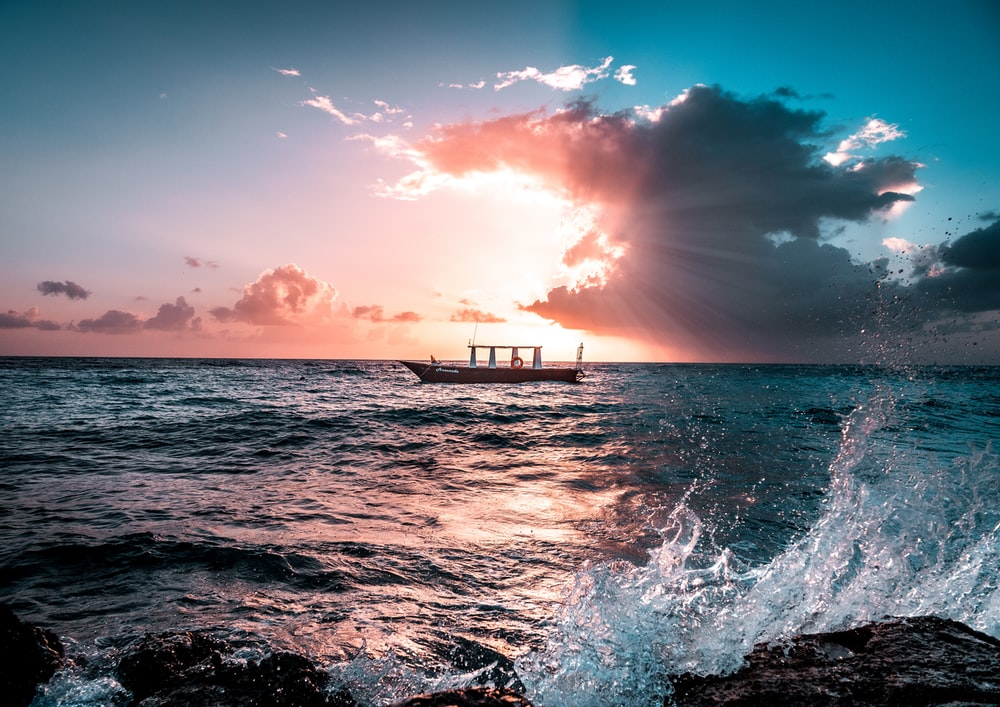 fishing boat in seat during sunset