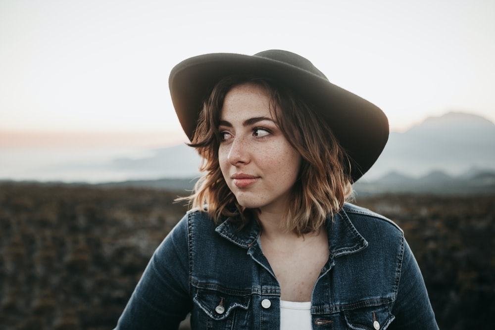 smiling woman wearing black hat and blue denim top