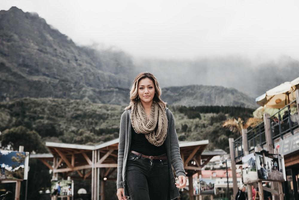 woman wearing black denim bottoms standing near building