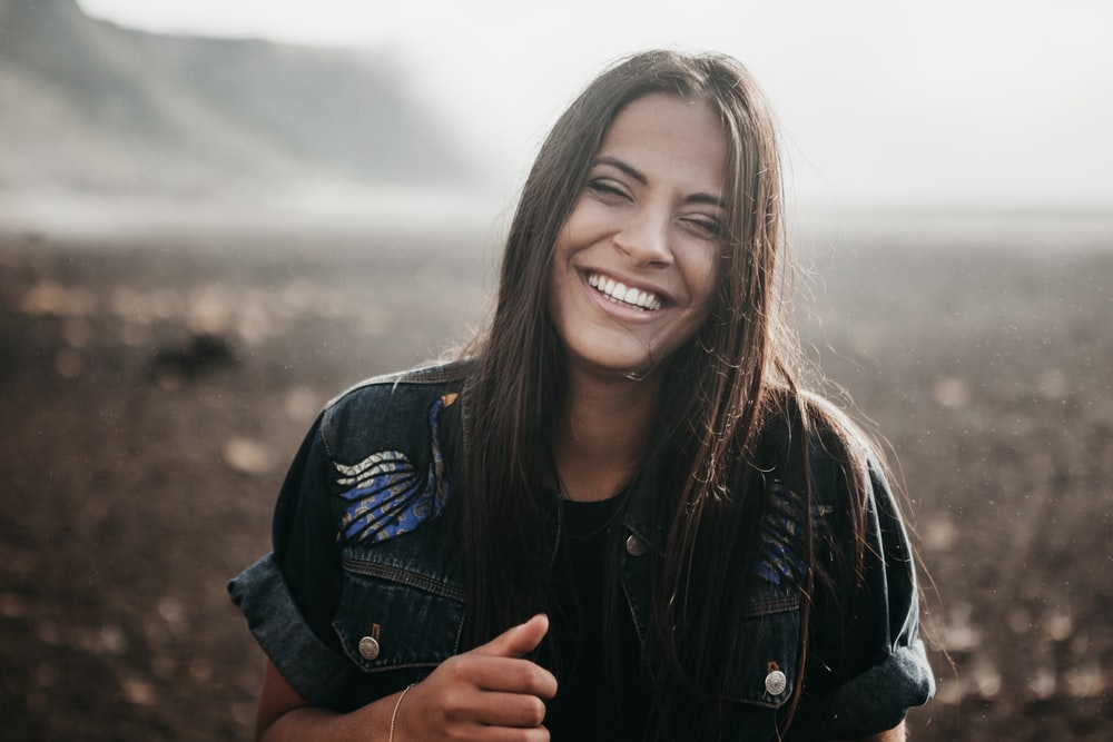 girl smiling in selective focus photography