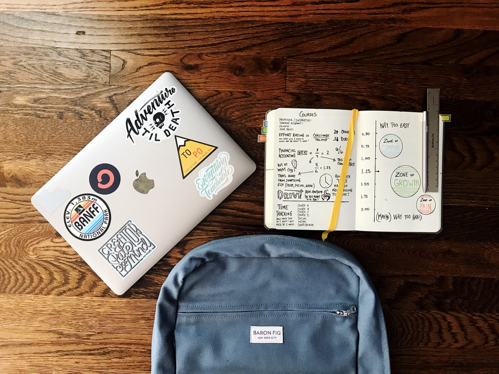 flat lay photography of blue backpack beside book and silver MacBook
