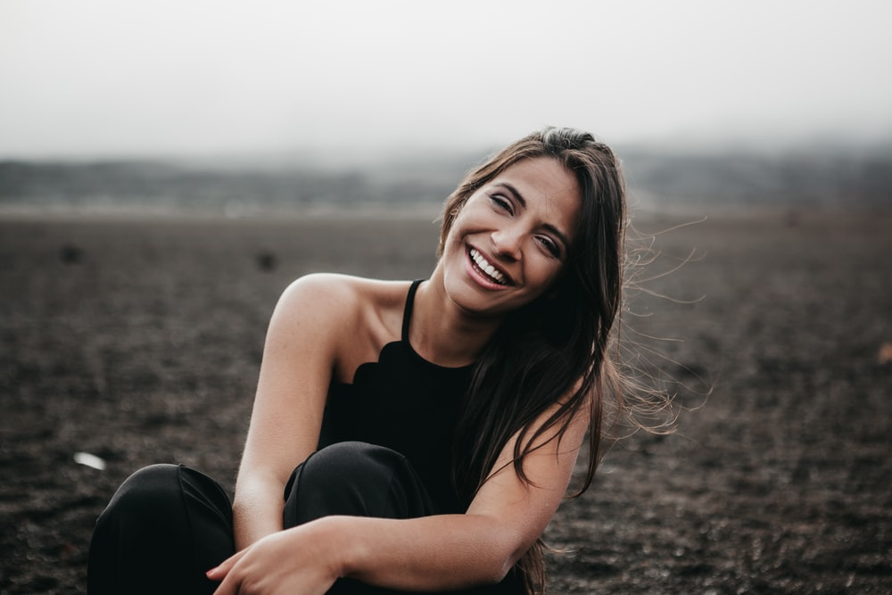 woman laughing while sitting on ground