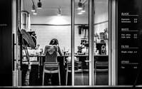 grayscale photography of woman inside cafe