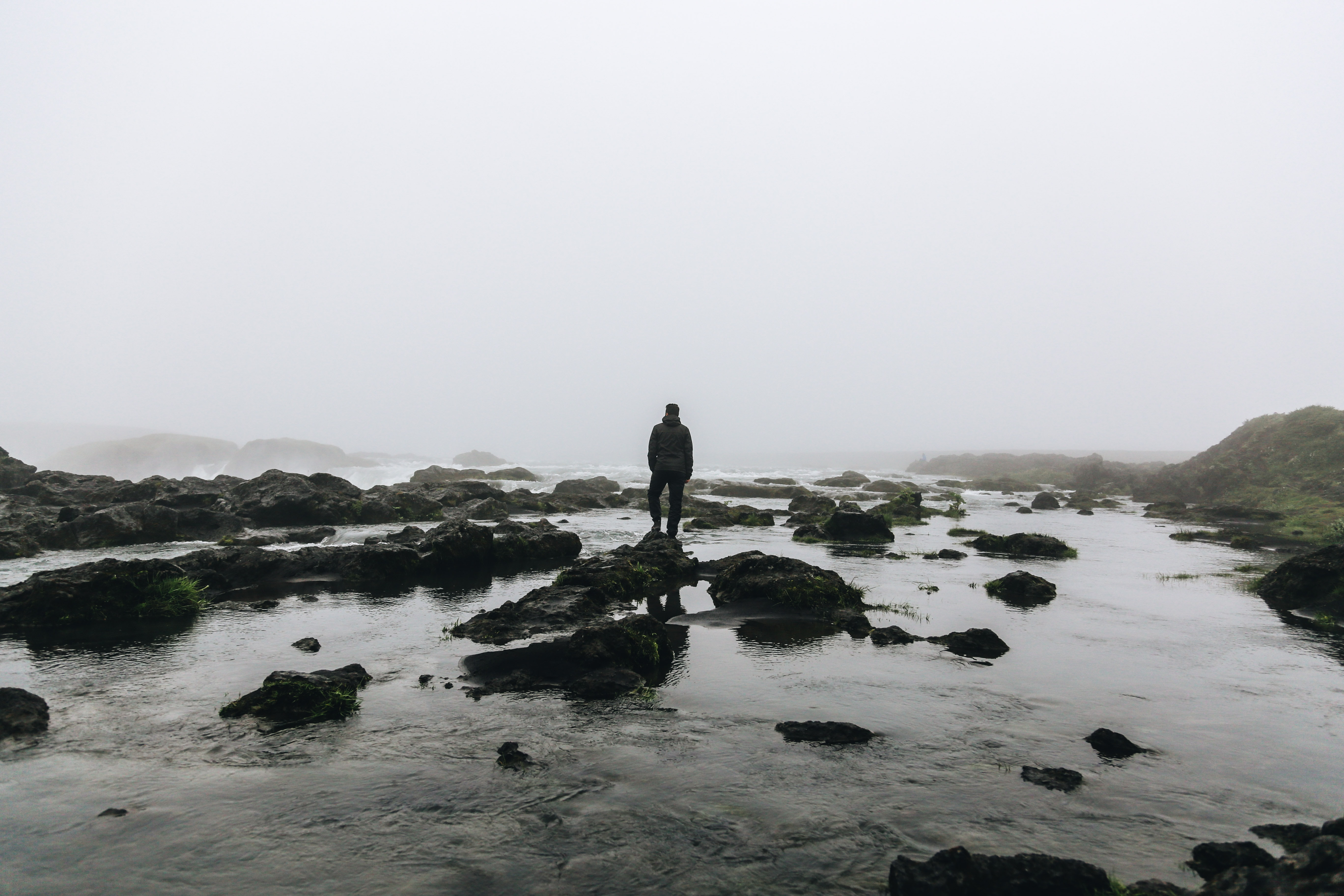 silhouette of person standing on stone surrounded by water during daytime