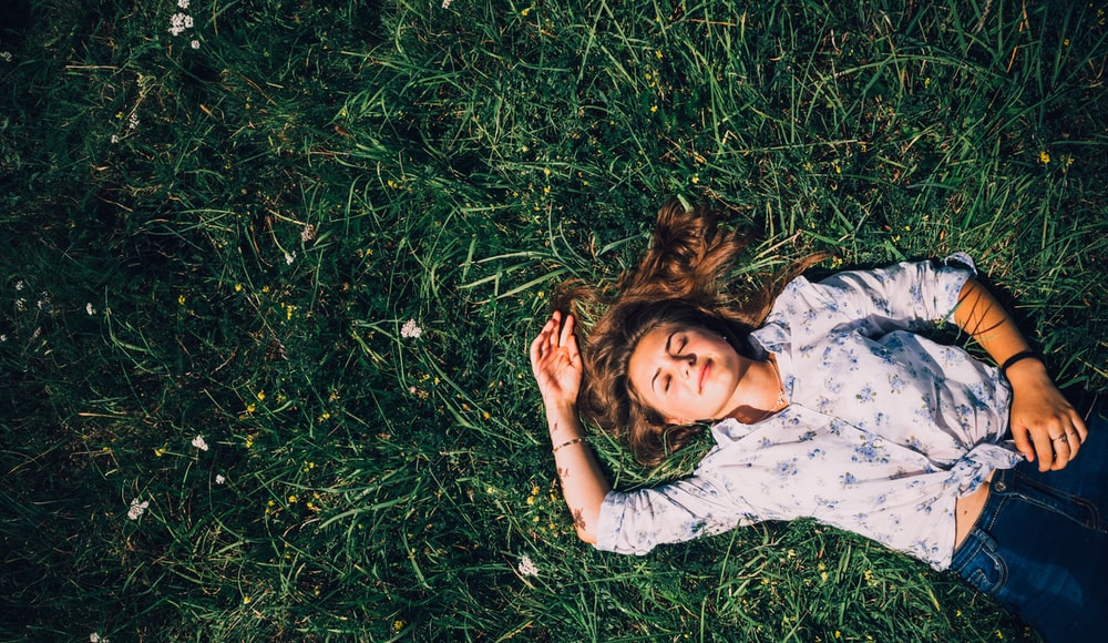woman lying on grass during daytime