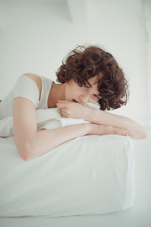 woman laying on white bedding