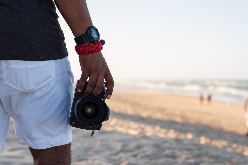 person's right hand holding black DSLR camera during daytime