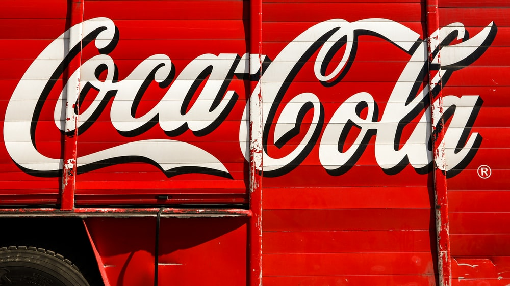 close-up photography of red and white Coca-Cola trailer