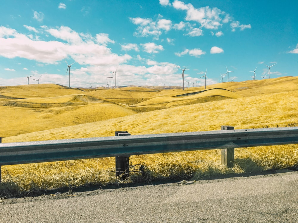 gray road barrier near wind farm