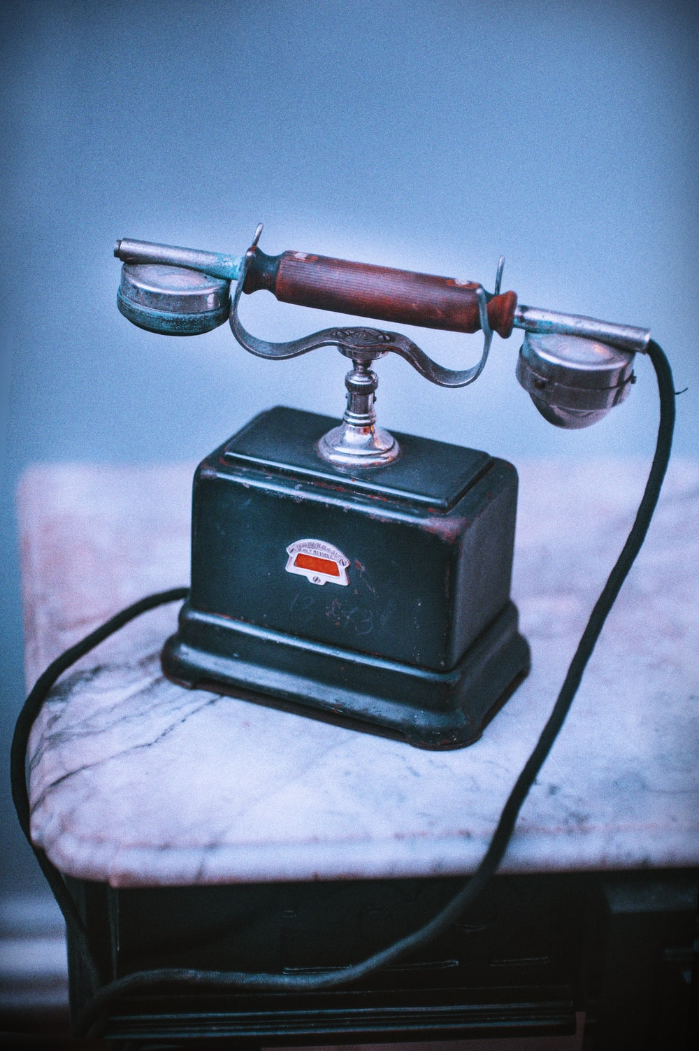vintage blue and brown telephone on beige surface