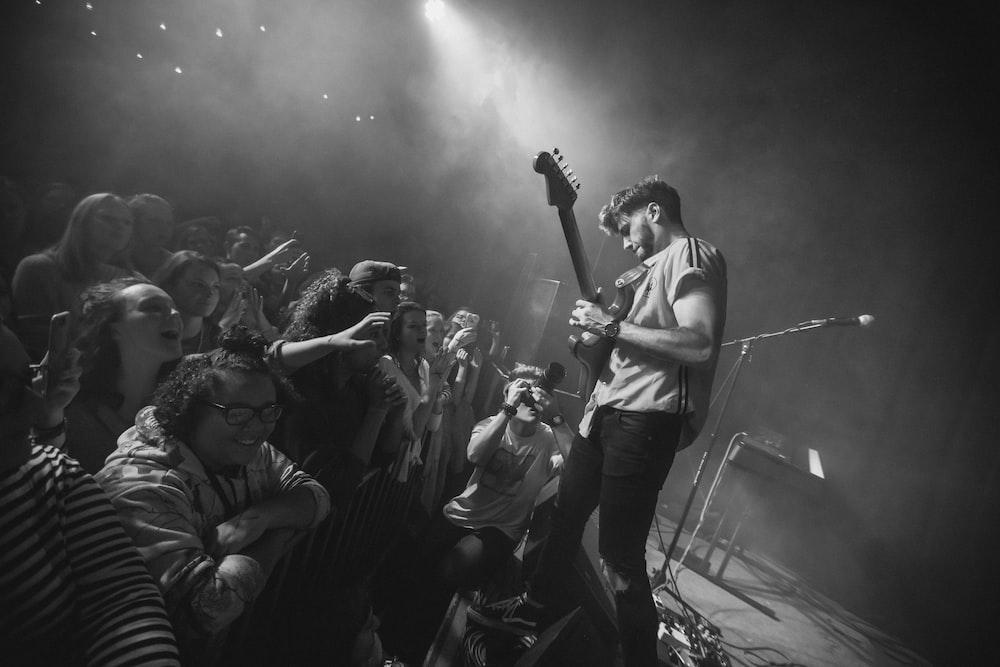 man playing guitar facing fans