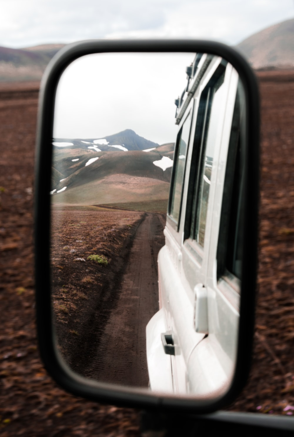 mountain range seen from vehicle wing mirror