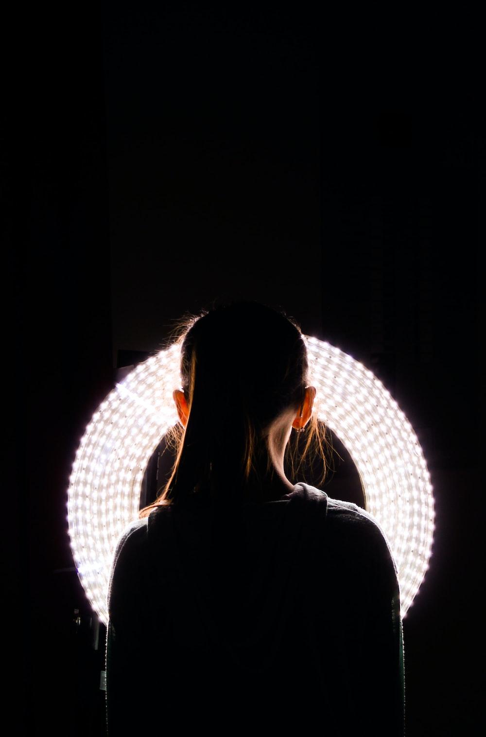 woman standing near round white vanity light
