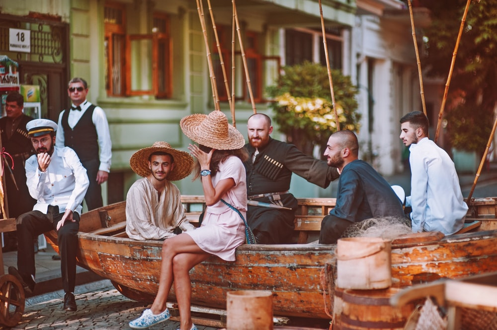group of people sitting on boat on road