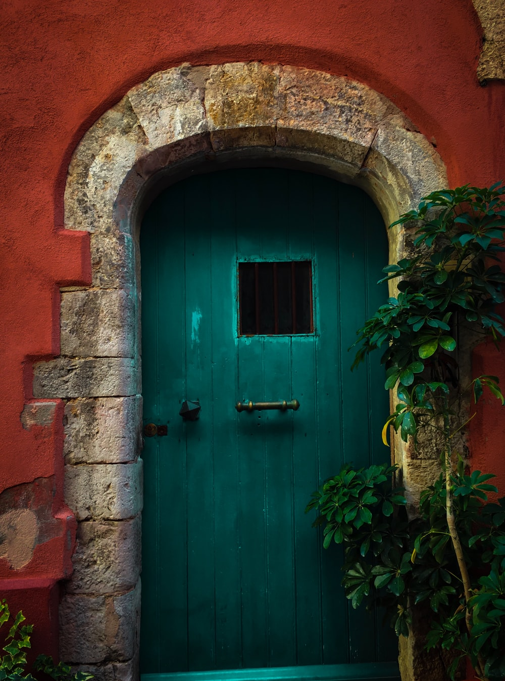green door on a red concrete house