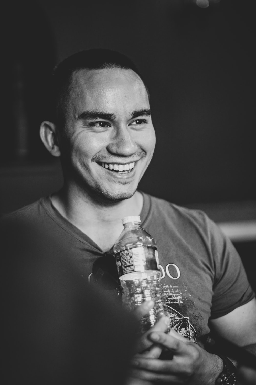 smiling man holding clear bottled water