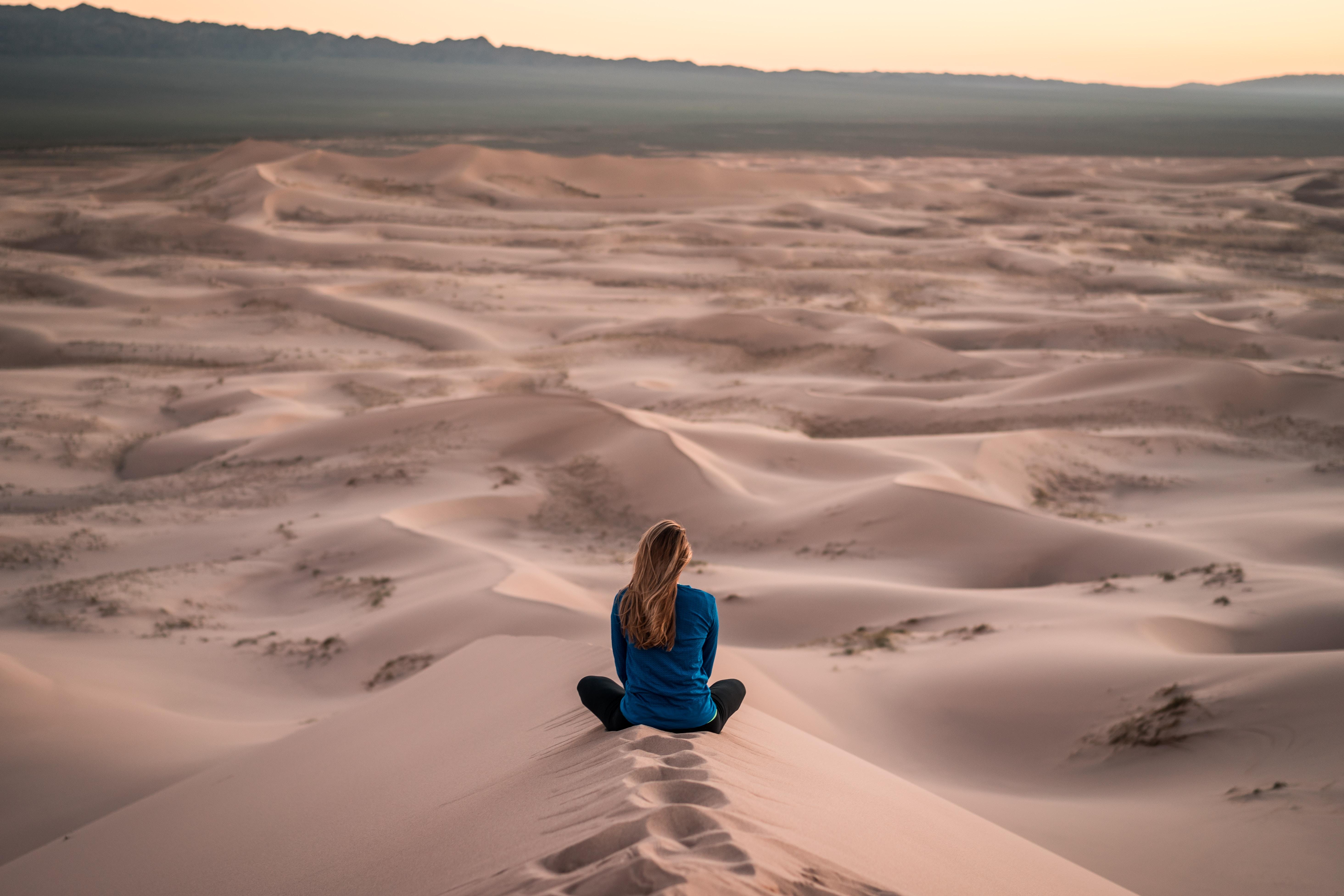 woman sitting on sand field