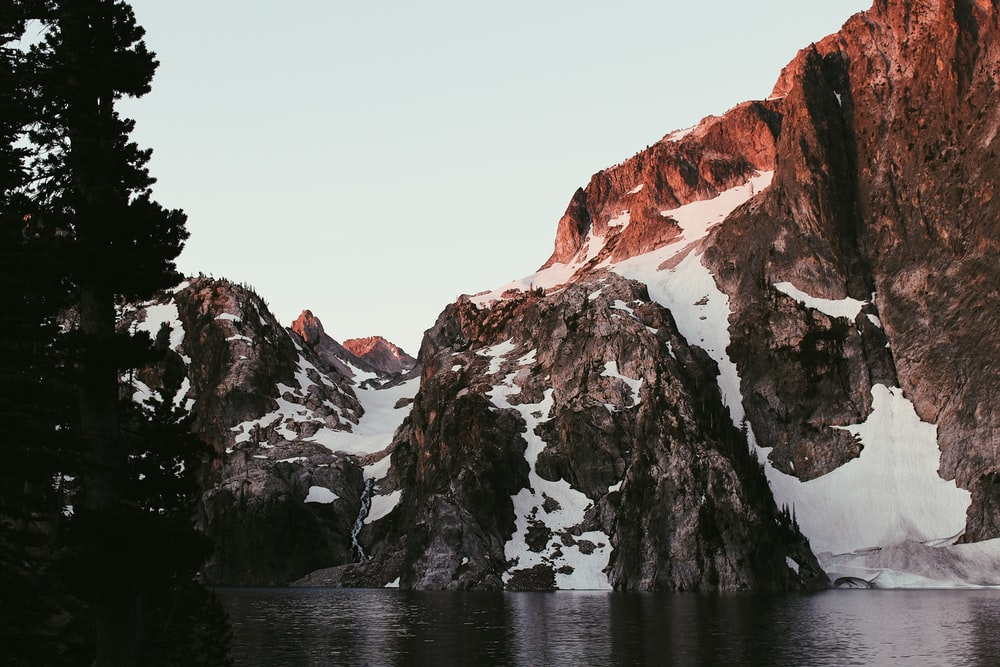 mountain covered with snow on body of water